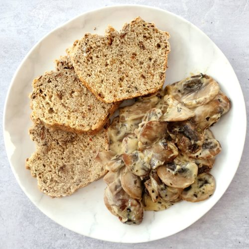 Close cropped overhead shot of mushrooms on a white plate with 3 arranged slices of soda bread.