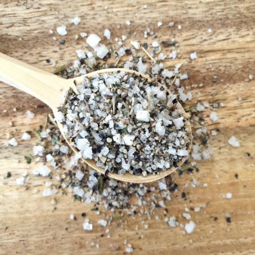 Close up overhead shot of flavoured sea salt spilling out of a wooden spoon.
