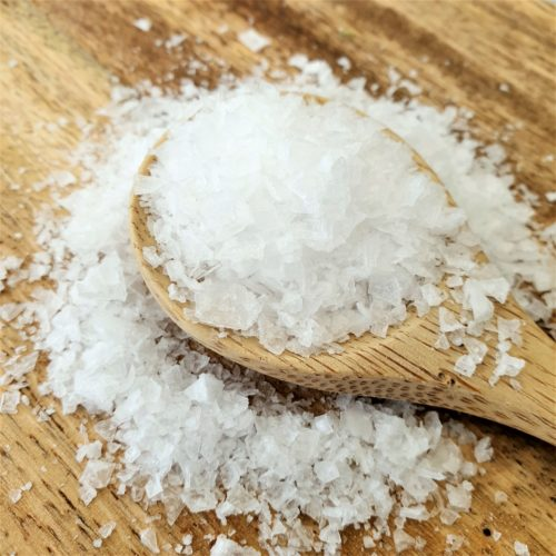 Close up of sea salt spilling off a wooden spoon onto a wooden board.