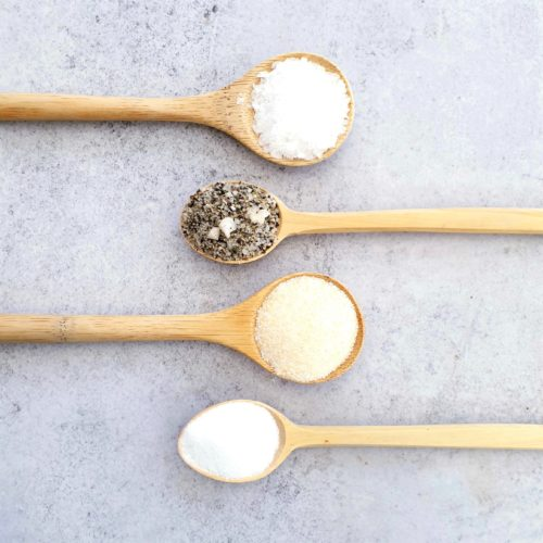 4 wooden spoons on a pale background each with a different type of salt. 2 spoons each come into the frame from the left and the right.