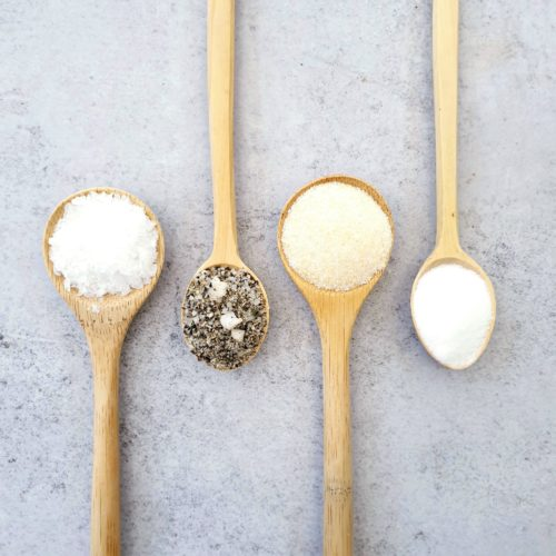 4 wooden spoons on a pale background each with a different type of salt. Sea salt, flavoured, table & garlic. Spoon are lined up with 2 pointing to the top and 2 to the bottom.