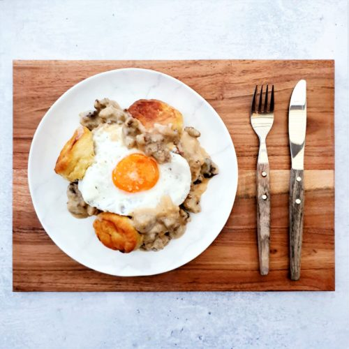 Flatlay shot of a plate of biscuits, gravy and unbroken fried egg on a serving board with cutlery laid straight to the right of the plate.