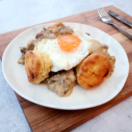 Angled shot of a plate of biscuits, gravy and unbroken fried egg on a serving board with cutlery in the distance.