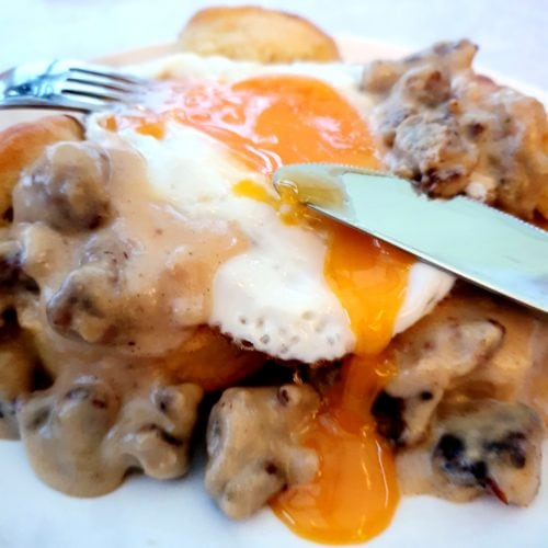 Sausage Gravy shown served on a plate on top of buttermilk biscuits with a fried egg with runny yolk.