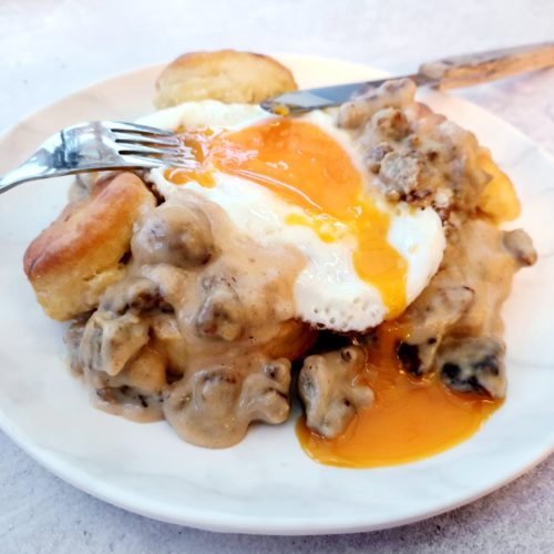 Wide shot of gravy and biscuits with a runny fried egg. Cutlery placed as being eaten.