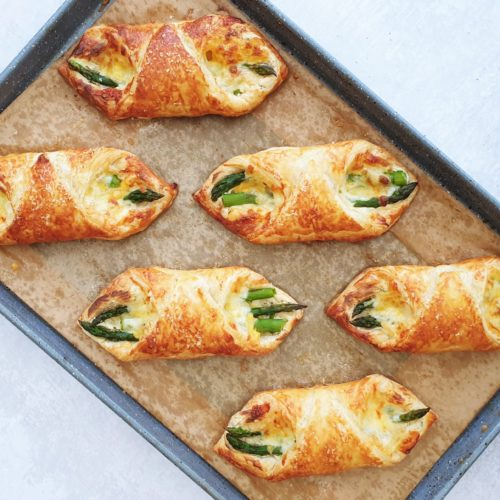 Tray of fresh from the oven puff pastry asparagus wraps shown from overhead at a diagonal angle