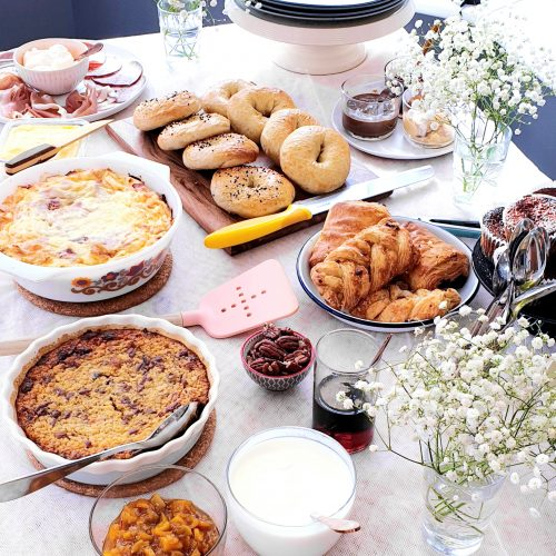 Angled shot of a brunch buffet table showing the food ready to be served. Egg casserole show to the top left.