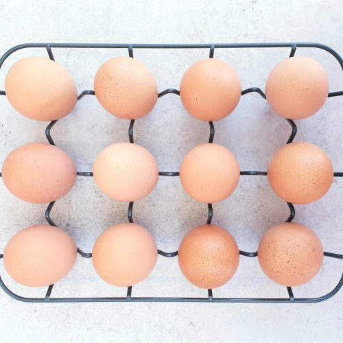 Overhead shot of 12 pale eggs in their shell on a pale blue background sitting in a dark grey wire rack.